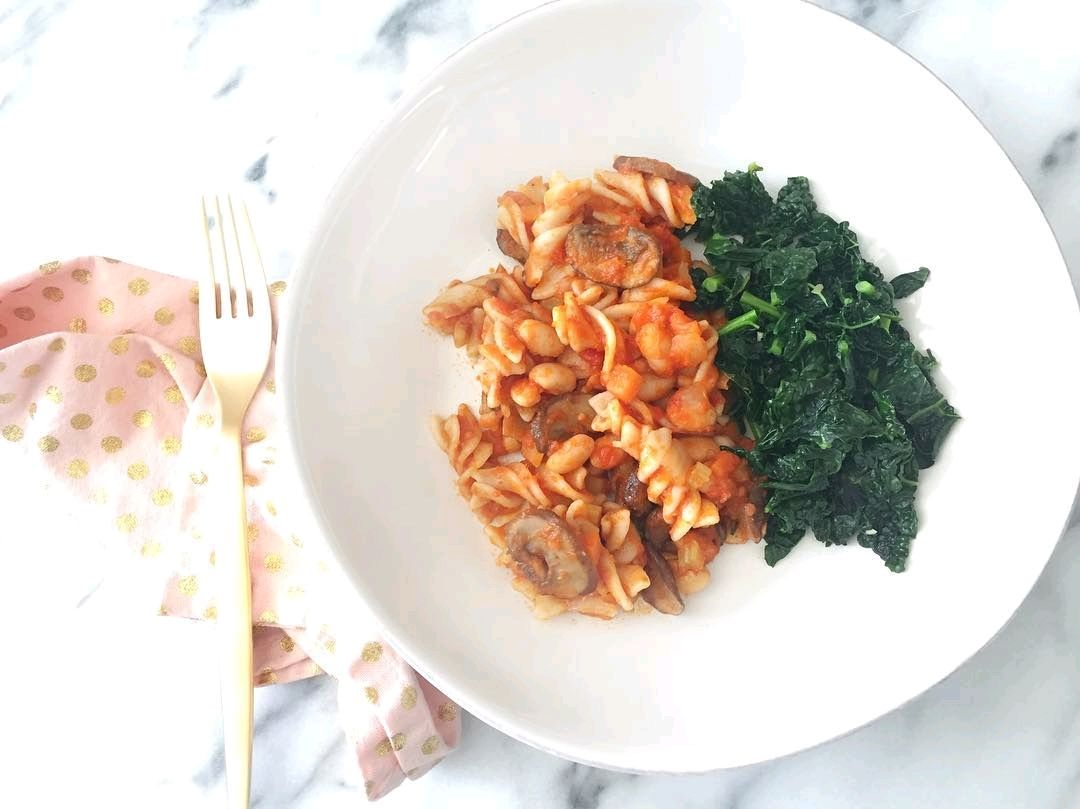Brown rice pasta with a white bean and mushroom bolognese, and garlic kale